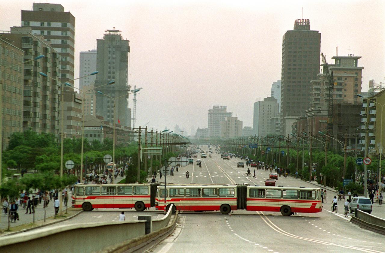 Két busz alkot blokádot a Tienanmen tér felé a Jianguomen sugárúton 1989. május 21-én. Az előző nap hirdették ki a rendkívüli állapotot Pekingben, a tüntetők pedig blokádot húztak a tér köré, hogy kirekesszék a katonai erőket. Csak két héttel később fog majd lecsapni a kínai hadsereg a demonstráló diákokra.