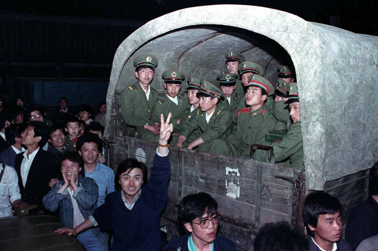 Diákok csoportja vesz körül egy négyezer fős katonai konvojt Peking külvárosában 1989. május 20-án. Meg akarják állítani a katonák útját a Tienanmen tér felé, ahol a demokráciát követelő diákok összegyűltek.