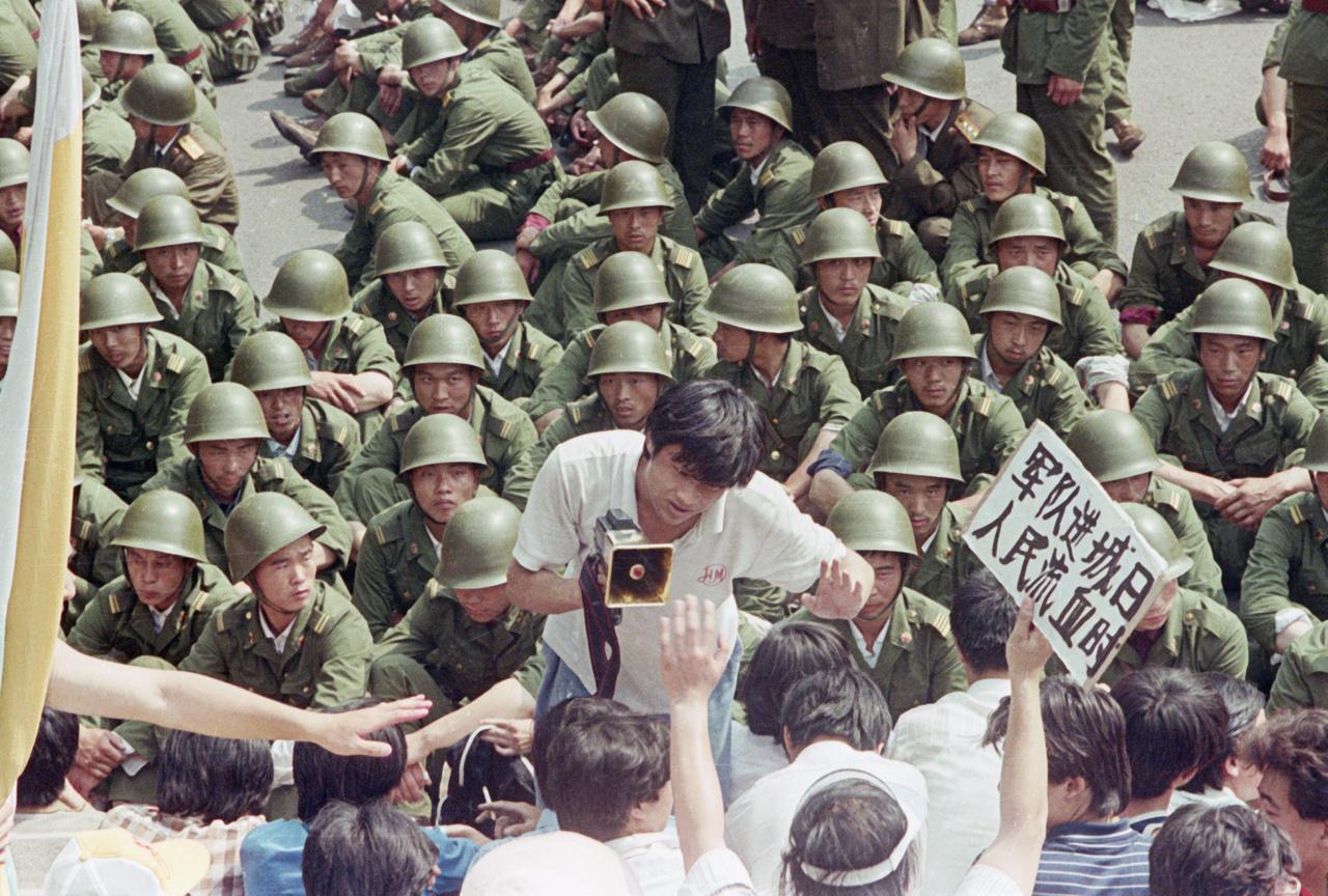 Katonák veszik körül a tüntető tömeget a Tienanmen téren. A demonstrálók élén egy fiatal, hangosbeszélővel a kezében.