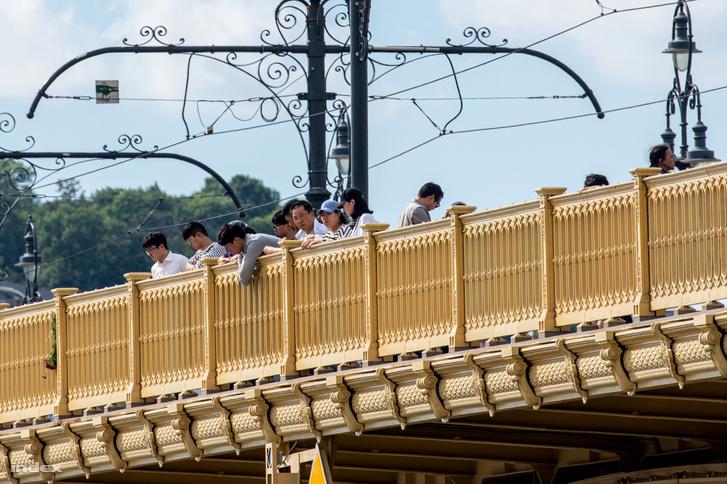 Emberek nézik a mentést a hídról, ők feltehetően az áldozatok hozzátartozói, mivel a szakaszt a rendőrség lezárta a gyalogos forgalom elől.