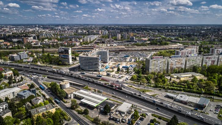 Dél-Buda Városközpont közlekedési csomópontja autópályákkal, vasúttal, metróval és az épülő Budapest One épülettel. Távolban az Etele Plaza, a villamos végállomás és a buszpályaudvar látszódik.
