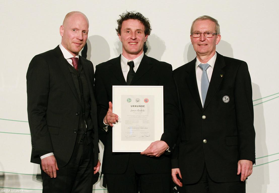 Matthias Sammer, a Német Labdarúgó Szövetség sportigazgatója, Radoki János (középen), aki bemutatja a labdarúgó edzői engedélyét és Rainer Milkoreit, a Német Labdarúgó Szövetség alelnöke, a Kameha Grand Hotelben az edzői- és technikai fejlesztési képzés díjátadó ünnepségén Bonnban 2012. március 21-én