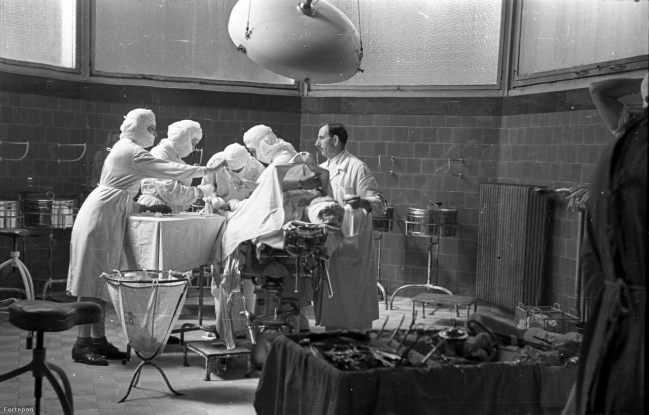 Szent János kórházApagyi kilesett a folyosóra. Derűs ez a kórház.Ő szereti a légkört, a harmincas évekNagyvonalú formakezelését, a levegős tereket,Az utcaszéles folyosókat. AhogyÁttűz a nyári nap az üvegtéglákon.A színskálát együtt dolgozták ki a kollégákkal,S ő óvta meg eredeti képébenA pepita padlócsempés lépcsőházat,Ő, a tekintélyes ideggyógyász, személyesenCsavarta ki a csákányt egy munkás kezéből, mielőtt még...