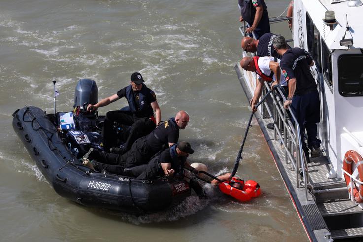 Bezuhant a Dunába a mentés egyike résztvevője a kiemelés helyszínén, amikor megpróbált átmászni a pontonra egy gumicsónakból. A folyó sodrására jellemző, hogy egy fekete gumicsónakkal kellett az érintett után sietni többeknek, a vélhetően tapasztalattal rendelkező szakember is alig bírt ugyanis megkapaszkodni a helyszínen lévő hajók oldalában.