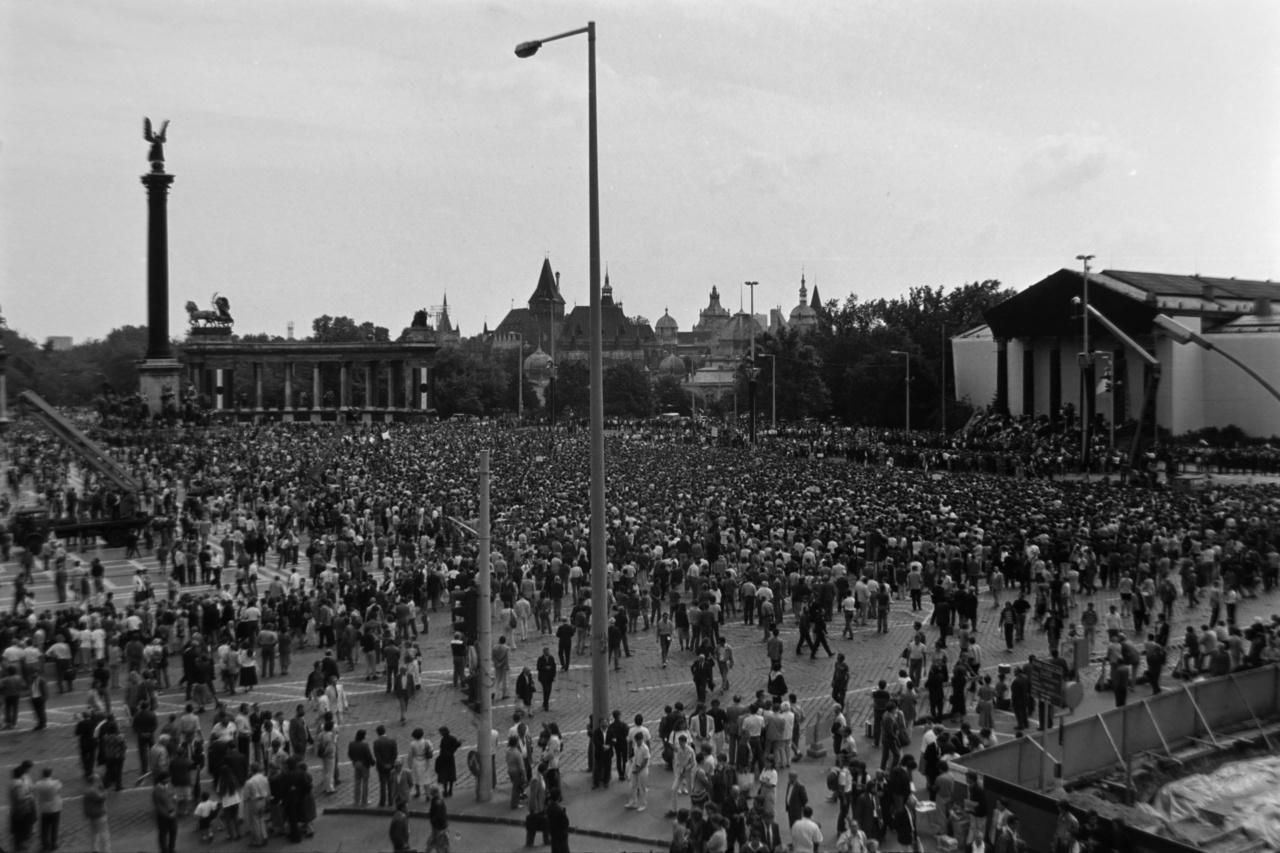 """A Magyar Televízió operatőre készítette ezt a felvételt a tér jobb oldalán álló emelőkosaras daruskocsibólAz 1988 májusában az ötvenhatos elítéltekből és a kivégzettek özvegyeiből alakult Történelmi Igazságtétel Bizottsága (TIB) szervezte a gyászszertartást. A tévé és a rádió egész nap közvetítette a gyászünnepséget, Bachman és Rajk eleve a kameraállásokat figyelembe véve komponálta meg a tereket. """"Magyarországon 1989. június 16-án temetés-tévé-forradalom volt. Temetni tudunk. Nem véletlen, hogy a nemzeti egységbe forrás, a forradalmi megigézettség, az újjászületés [...] éppen egy temetési ünnepségre esett. Az '56-os mártírok temetésén a Kádár-korszak alapdogmája, legitimitásának fundamentuma dőlt meg. '56 nem ellenforradalom, hanem forradalom. Kimondatott a varázsige, amelyet harminchárom évre el kellett felejteni. A nemzeti gyász napja a rendszerváltás népünnepélye volt""""– idézte fel később Lakner Judit."""