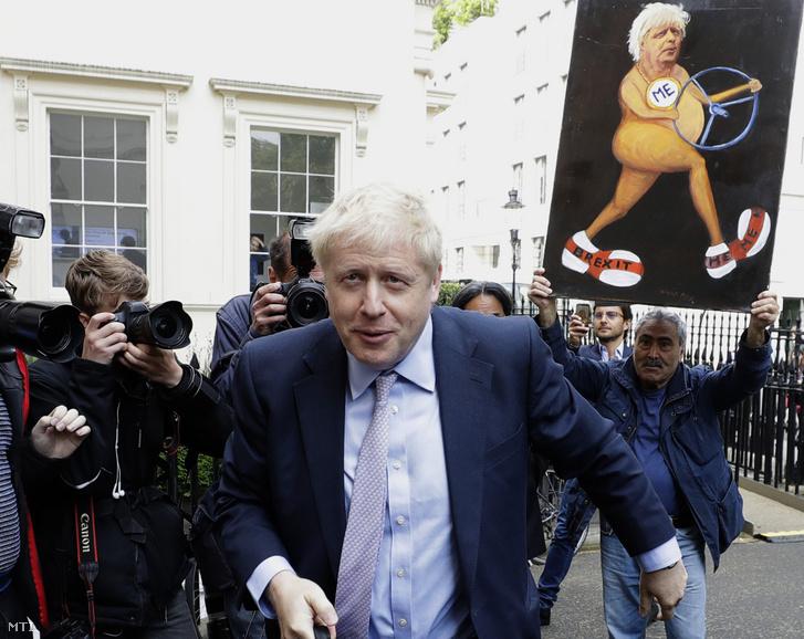 Boris Johnson volt külügyminiszter a keményvonalas tory Brexit-tábor frontembere érkezik a londoni kampányrendezvényére 2019. június 12-én. Mögötte jobbról Kaya Mar brit karikaturista a Johnsont ábrázoló alkotásával.