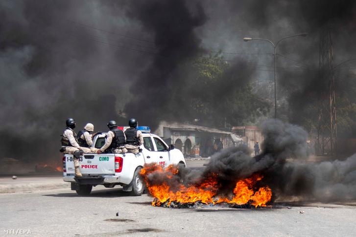 Tüntetők által felgyújtott barikád mellett mennek rendőrök a haiti elnök, Jovenel Moise lemondását követelő korrupcióellenes megmozduláson a fővárosban, Port-au-Prince-ben 2019. június 13-án.