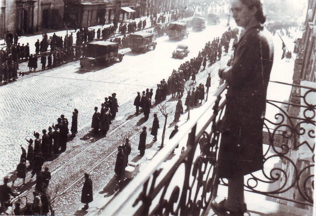 Kelemen tanár úr felesége, Franck Ilona 1944 márciusában, a német megszállás után a kassai Fő utca 90. erkélyén. Az utcán masírozó katonák és bámészkodó tömeg.