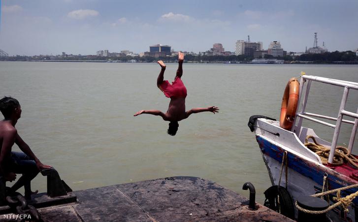 Fiatalok hűsölnek a Gangesz partján Kolkatában 2019. június 11-én. Indiában hőhullám tombol, a hőmérséklet régiótól függően meghaladja a 36-48 Celsius-fokot.
