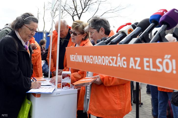 Egy nő aláírja az aláírásgyűjtő ívet a Fidesz országos aláírásgyűjtő akciójának kezdetén tartott sajtótájékoztató előtt az újpesti piacnál felállított aláírásgyűjtő standnál 2019. április 6-án