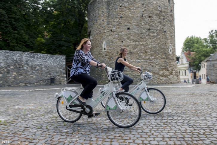 Ketten a pécsi kerékpár szóösszetételből alkotott PécsiKe elnevezésű közösségi kerékpármegosztó rendszer kerékpárjait használják az átadó napján a pécsi Barbakán téren 2019. június 19-én.
