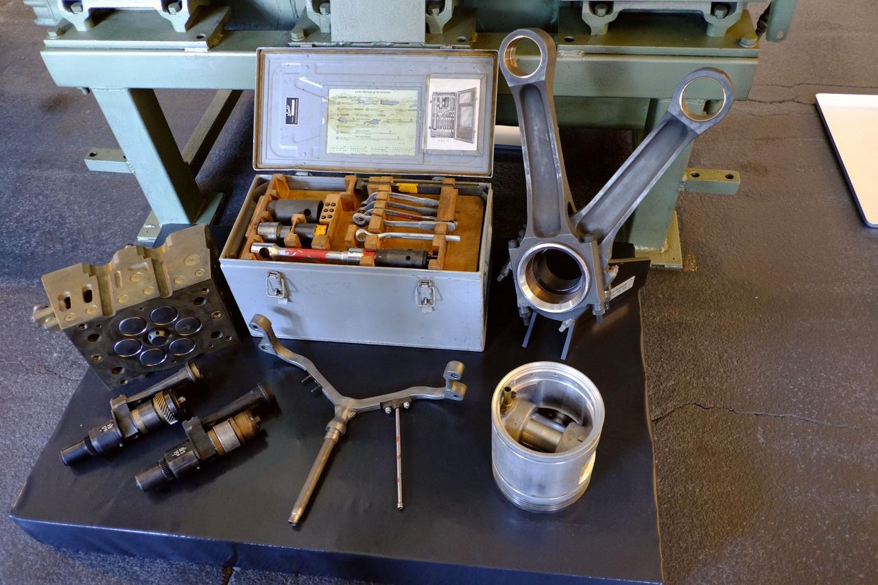 Ha minden igaz, akkor ez az 1949-es MD650 dízelmotor hengerfeje, adagolószerelő szerszámkészlete, hajtórúdjai (V-ben összekapcsolva!), de az a dugattyú túl pici, talán a kompresszoré lehet? nem volt felirat mellé