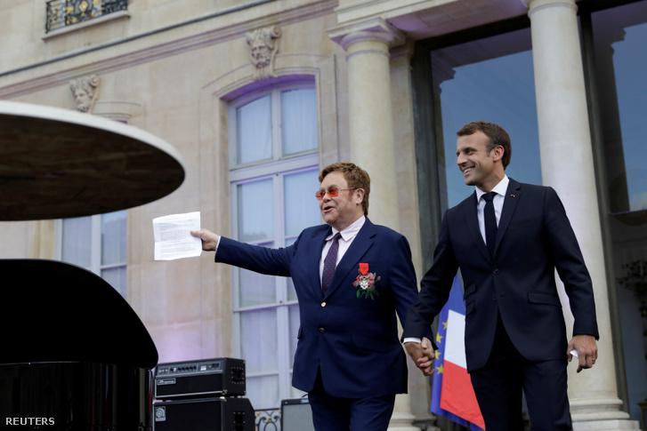 Emmanuel Macron francia elnök és Elton John kézen fogva jönnek ki az Elysée-palota udvarára 2019. június 21-én.