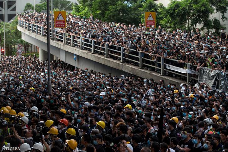 A kiadatási törvénytervezet visszavonását követelik tüntetők a rendőrség székházánál Hongkongban 2019. június 21-én.