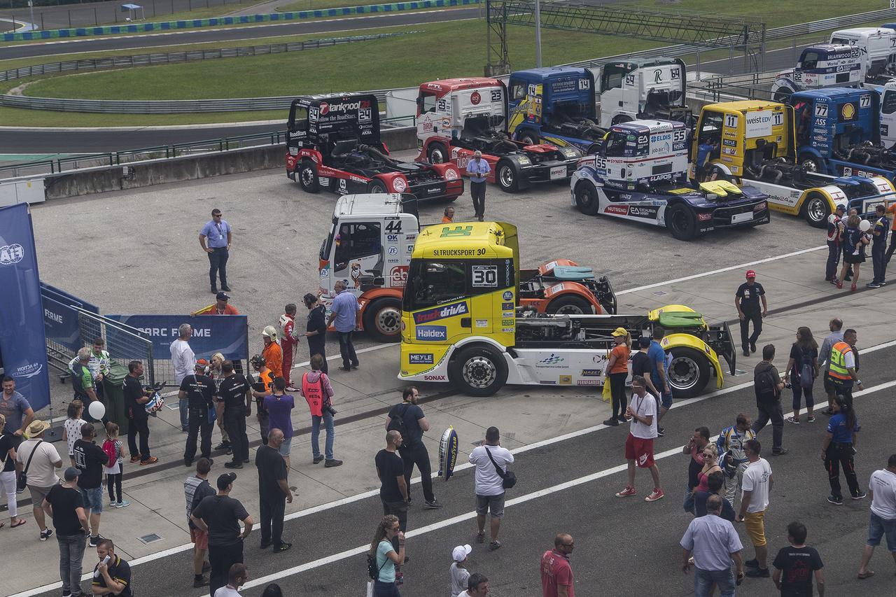 Érkeznek a parc fermé területére a kamionok. Ez az a terület, ahol bármilyen motorsport rendezvény esetén tilos a versenyautókhoz akár egy ujjal is hozzáérni. Miután a tilalom feloldásra kerül, eszeveszett versenyfutás kezdődik a kevés idővel, ami szervizelésre rendelkezésre áll