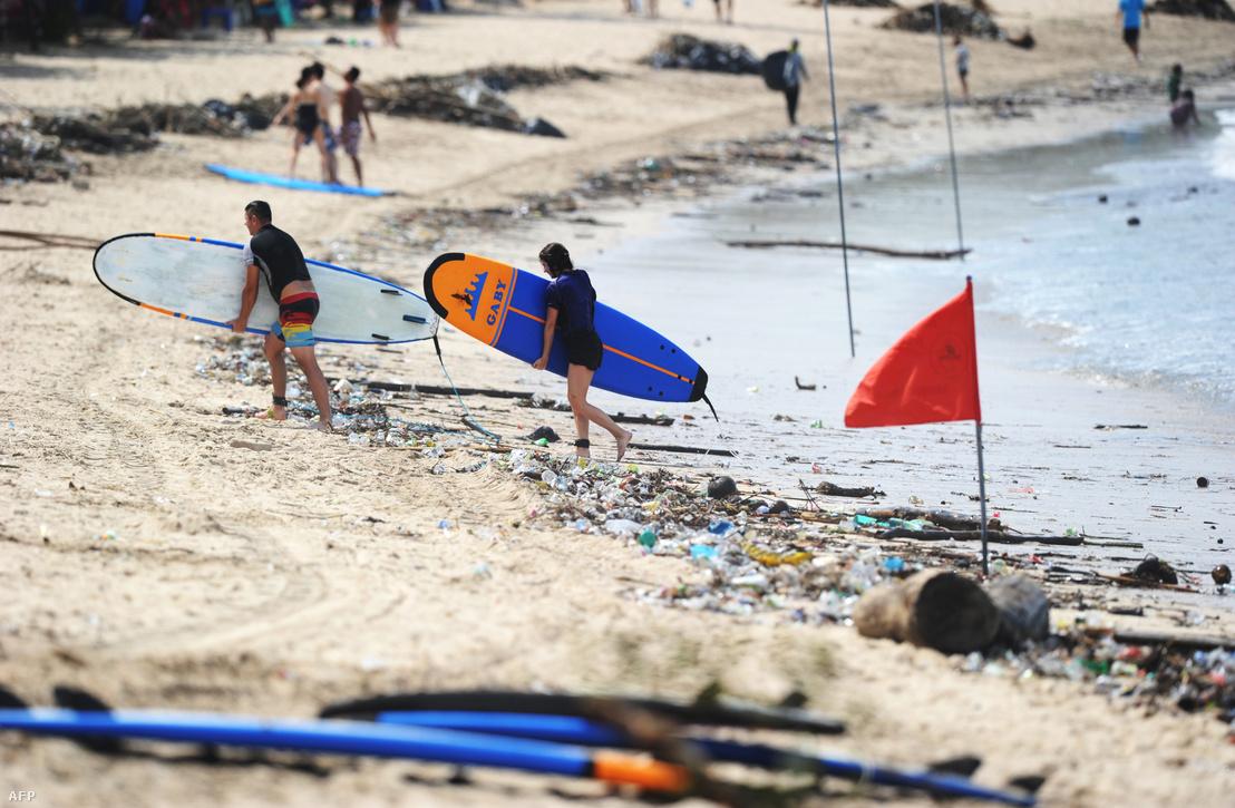 Szörfözők sétálnak át a kisodort hulladékkal teli Kuta Beach-en, Balin 2018. december 9-én.