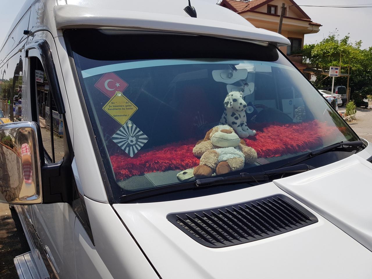 Műszerfal UV védelme és plüsskutya kiállítás kimaxolva. Sok autóban akár méretre gyártott szőnyeggel, dizájnos burkolattal védik a tűző nap ereje ellen a műszerfalat, ami ezen a klímán évek alatt képes szétrepedni, elporladni