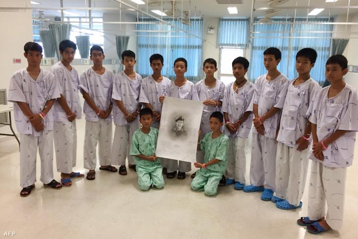 A thaiföldi Tham Luang-barlangban rekedt ifjúsági labdarúgócsapat, a Thai Wild Boars tagjai a Prachanukroh kórházban megmenekülésük után 2018. július 14-én. Középen a kezükben tartják a mentés közben meghalt Saman Kunan búvár képét.