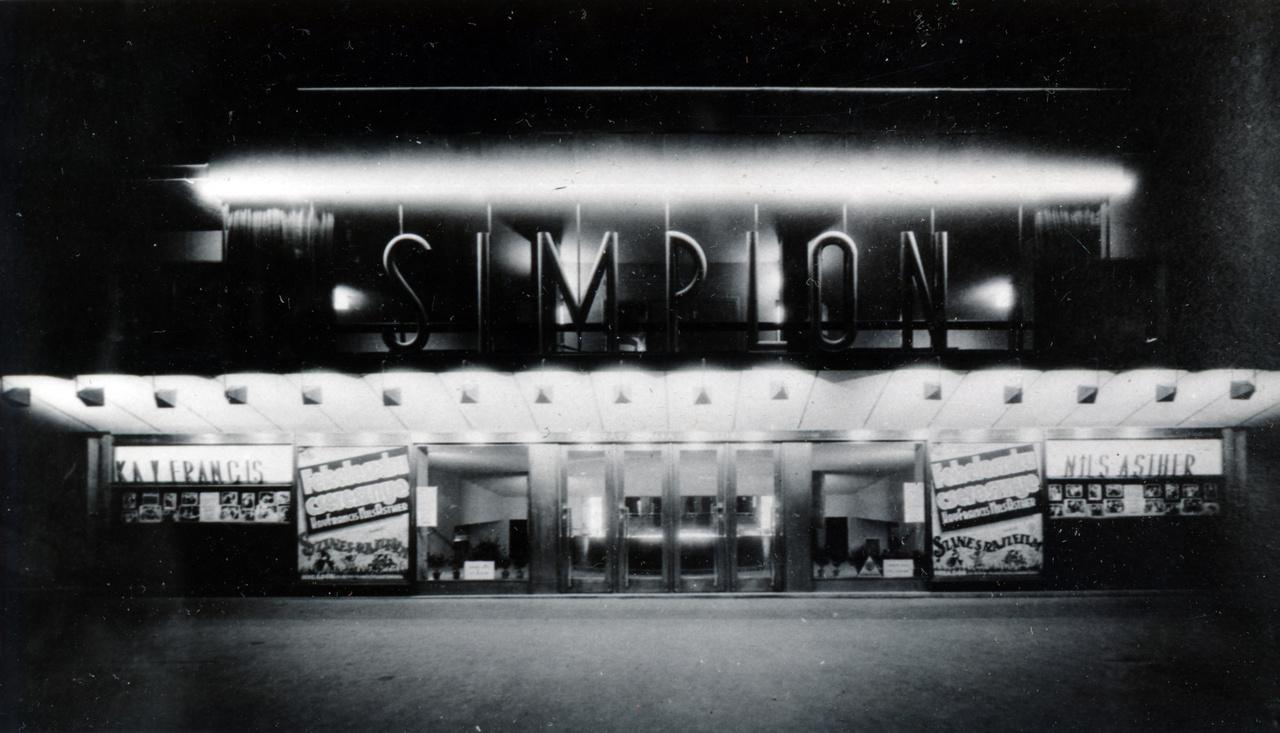 Ez pedig a ház aljában működő mozi bejárata, a SIMPLON felirattal. Érdekes, hogy teljesen más betűtípust használtak itt, mint a tetőn. Akár csak az Excelsior neonjainál, a Simplonnál sem törekedtek egységes arculatra.