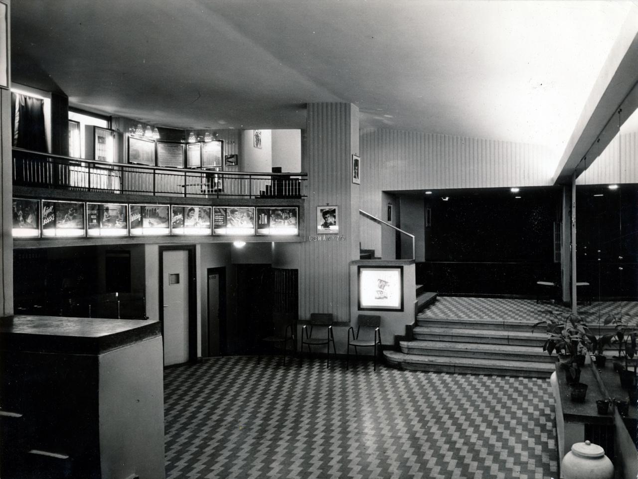 """Igazi friss dizájn az előtérben. A hátulról megvilágított plakátok, a """"dohányzó"""" felirat és a kockás padló egy hatvanas-hetvenes években épült moziban is lehetnének, de most még csak 1934-et írunk!"""