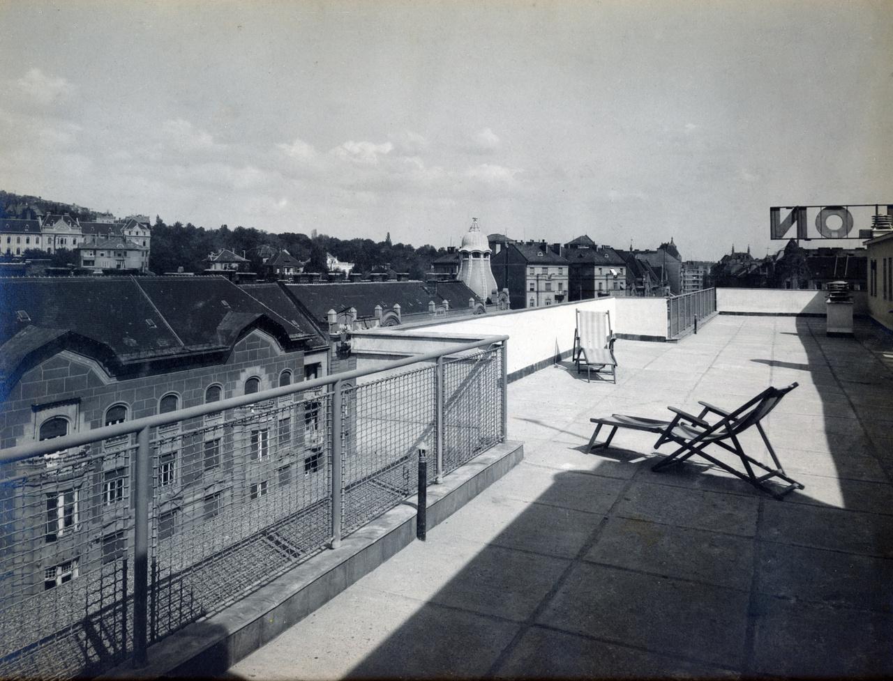 A Simplon volt az első modern bérház a fővárosban, szóval alighanem ez volt az első olyan is, aminek igazi nagyvárosi tetőterasza lehetett. A nyugágyak akár maiak is lehetnének. A háttérben a Móricz Zsigmond körtér egyik házának jellegzetes tetődísze, és a térre néző neonfelirat utolsó betűi látszanak.