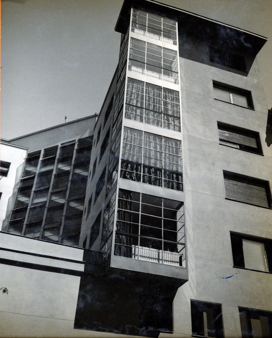 A homlokzaton végighúzódó üvegsávok mögött a felületes szemlélő talán lépcsőházat sejt. Sok helyen valóban ez volt a bevett szokás (a dessaui Bauhausnak is ilyen a lépcsőháza), de itt egy zárterkélysorról van szó. Ez volt az igazi dísze az épületnek a hegyesszögű sarkon is. Az üvegfalak mögött látszanak a függyönyök és a radiátorok, a kép baloldalán pedig ott az igazi lépcső.
