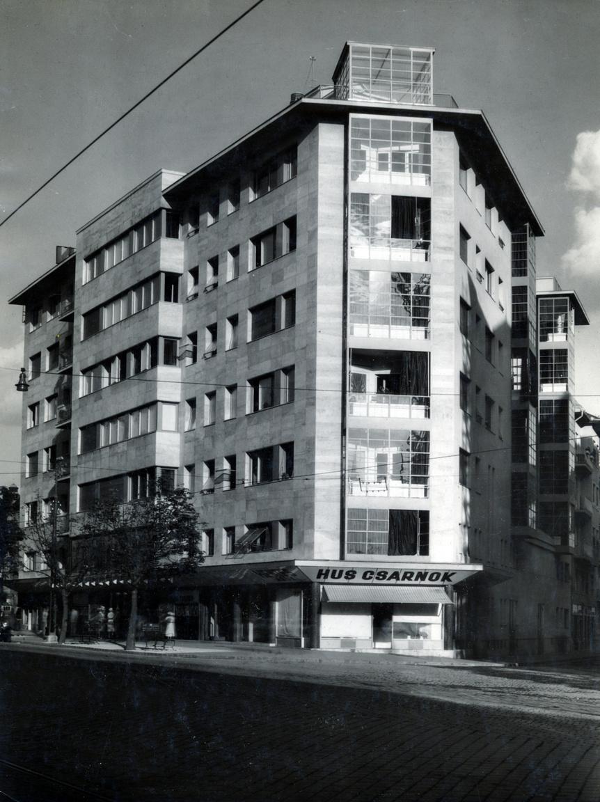 """A Simplon-ház egy hegyes szögű saroktelekre épült 1934-ben, a Móricz Zsigmond körtérnél, a Bartók Béla (akkoriban Horthy Miklós) útra. Ez volt az első modern stílusú bérház Budapesten. Az utána követekezők közül kevés van, amelyik el tudta érni ennek a színvonalát.Acélvázas szerkezete van, aminek egyetlen oka, hogy a lakásínséget úgy csillapította a főváros, hogy adómentességet adott a főútvonalak mentén épülő bérházaknak - feltéve, hogy időben elkészülnek. Ezt tempót pedig csak ezzel a technológiával lehetett elérni.A tető szintje fölé nyúló üveg """"toronydíszítményt"""" ma már hiába keressük, de a ház aljában meglepő módon azóta is működik a hentes. Manapság Ica mama húsboltjának hívják."""