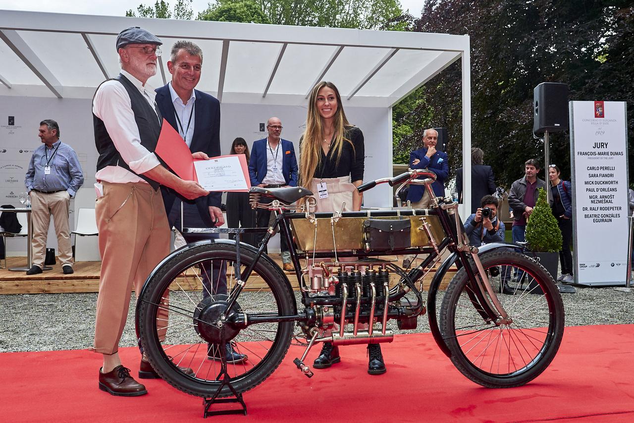 Még egy FN, 1905-ből. Alig két évvel a motorkerékpár-gyártás beindítása után a Fabrique Nationale d'Armes de Guerre már szenzációval jelentkezett: a világ első, sornégyes blokkjával, amelynek erejét kardántengely vitte a hátsó kerékhez. Második lett a kategóriában. A hölgy a zsűri tagja!