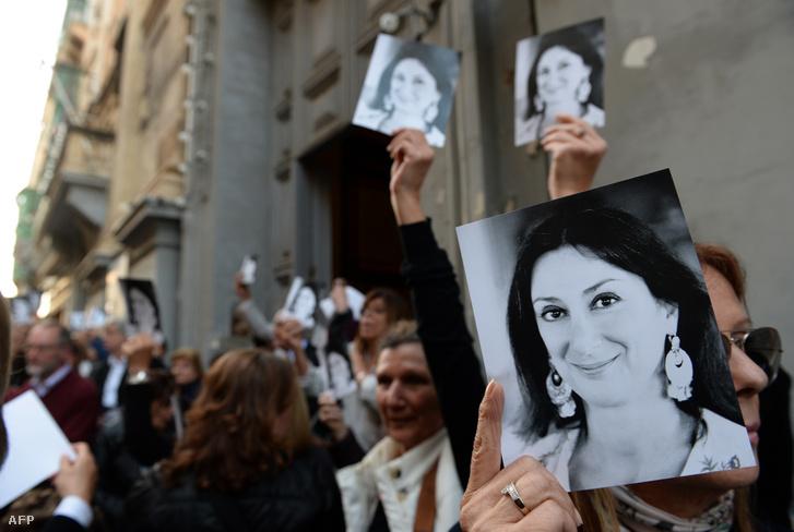 Emberek tartják kezükben Daphne Caruana Galizia képét, a máltai Szent Ferenc templomban tartott megemlékezés után 2018. április 16-án