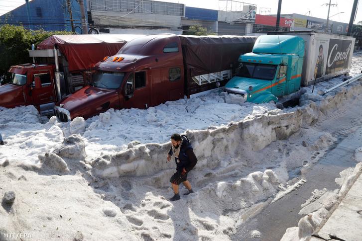 Jégdarabkákkal borított utcán megy egy férfi egy hatalmas vihart követően a mexikói Guadalajarában 2019. június 30-án