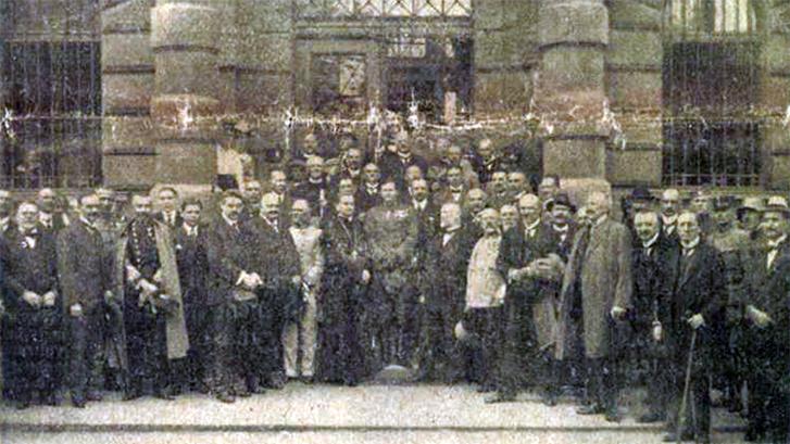 A DIKTATÚRA TÚSZAINAK TALÁLKOZÓJA A GYŰJTŐFOGHÁZBAN. A középen áll József Ferenc királyi herceg. Tőle jobbra: Mikes János gróf püspök, Szurmay vezére ezredes, Heinrich Ferenc, Huszár Károly, stb. Balra: Simonyi-Semadam miniszterelnök, Kirchner altábornagy, stb. Forrás: Ország-Világ, 1920 / Arcanum adatbázis