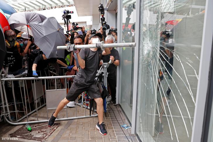Tüntető töri be a hongkongi városi tanács épületének bejáratát 2019. július 1-én