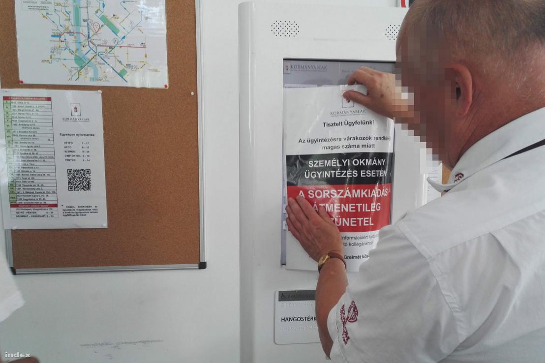 Biztonsági őr kiragasztja az Andrássy úti kormányablak ajtajára a szünetelésre vonatkozó tájékoztatást 2019. június 17-én