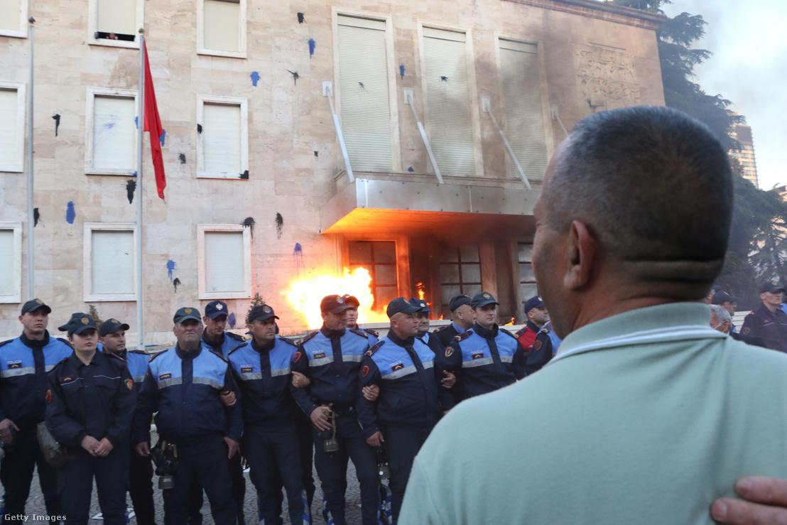 Egy Molotov-koktél robban a rendőrök mögött egy kormányellenes tüntetésen, Tiranában. 2019. május 11.