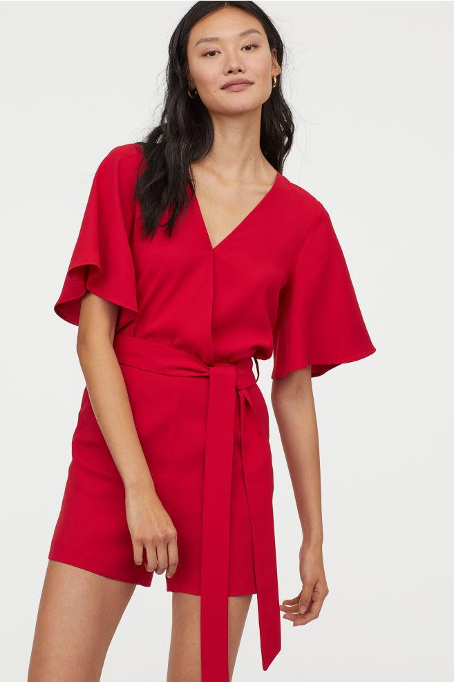 Extra nőies a H&M piros overallja, amely az övnek köszönhetően centikkel karcsúbbnak láttatja a derekat. 9995 forintért veheted meg.