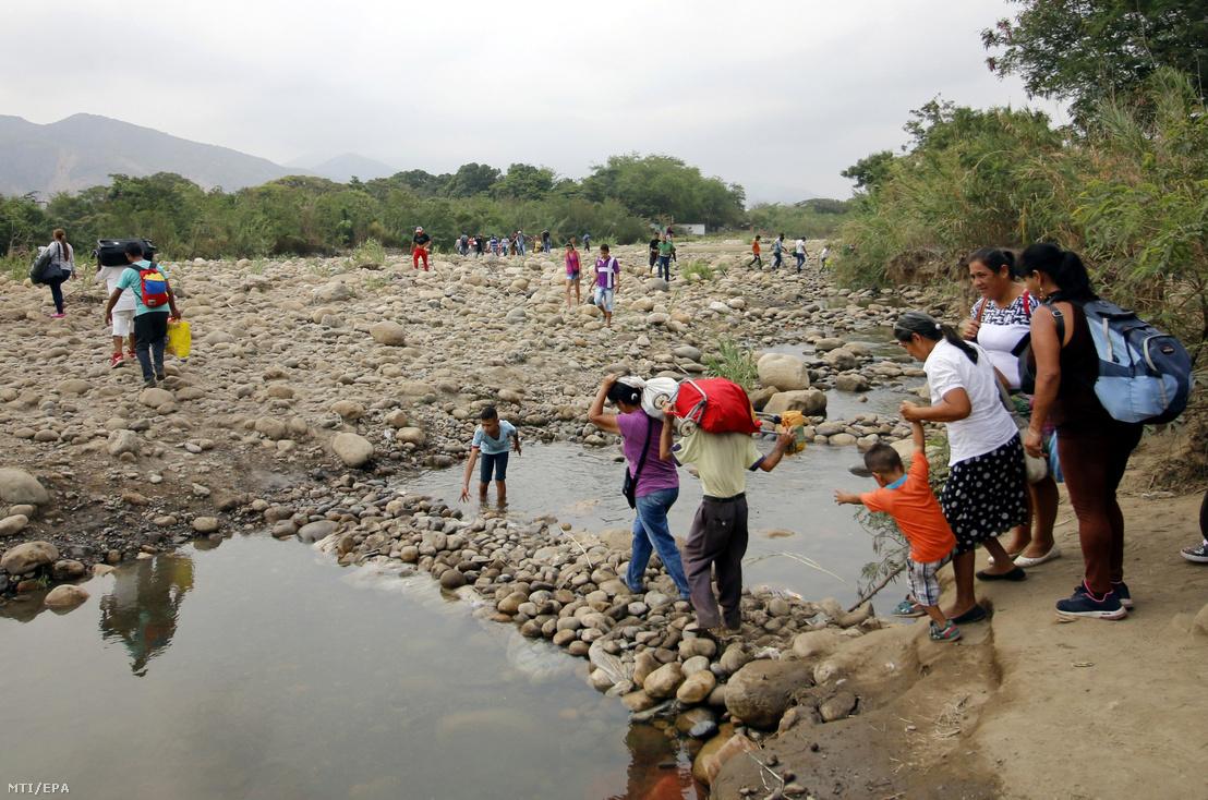 Venezuelai diákok szüleikkel átkelnek a Tachira folyón Venezuelából Kolumbiába a Francisco de Paula Santander híd közelében 2019. március 6-án. Sok venezuelai szülő a szomszédos országba küldi tanulni a gyermekét abban a reményben, hogy ott magasabb színvonalú oktatásban részesülhetnek, mint válság sújtotta hazájukban.