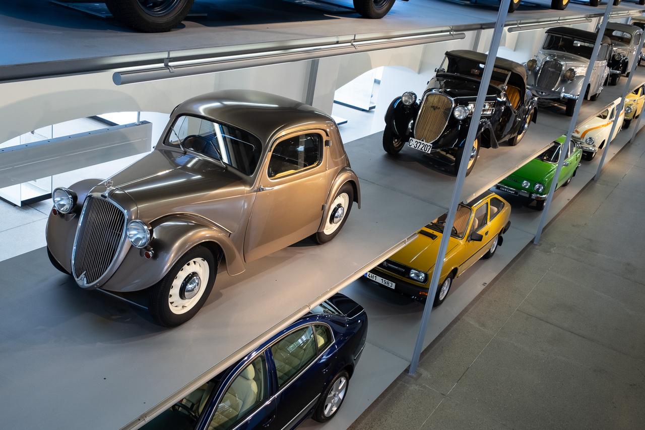 Előtérben egy rettentő csinos Skoda Rapid II Cabrio de Luxe. A Typ 914-es gyári kódú autó 1937-ben készült, 1,4-es motorja 31 lóerőt tudott, mellyel épp megfutotta a 100-at