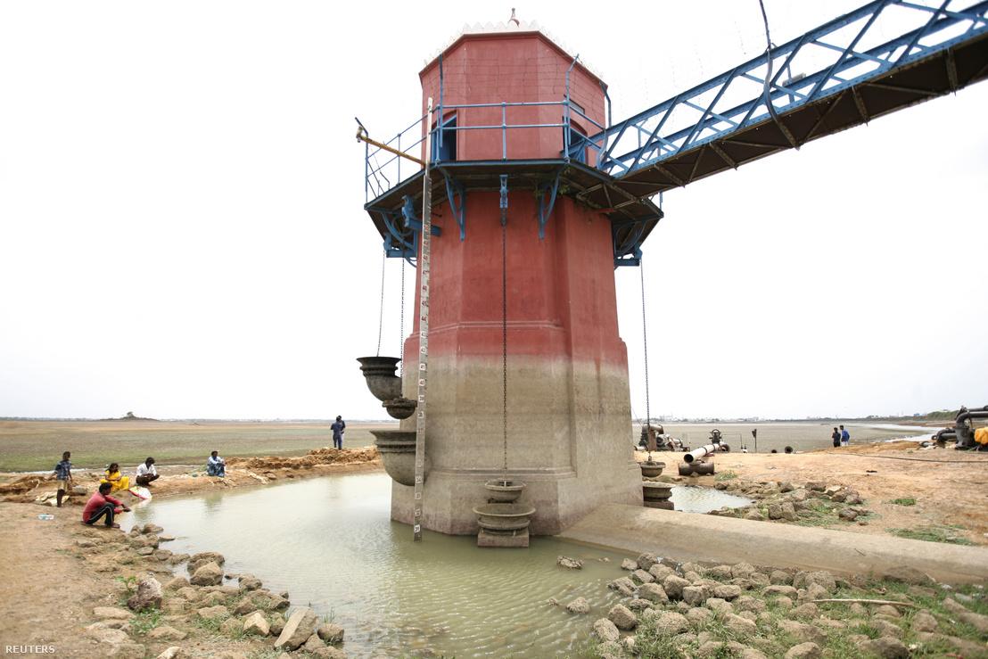 Emberek ülnek a Puzhal tónál található torony körül, aminek oldalán a korábbi vízmagasságot lehet látni 2019. június 20-án