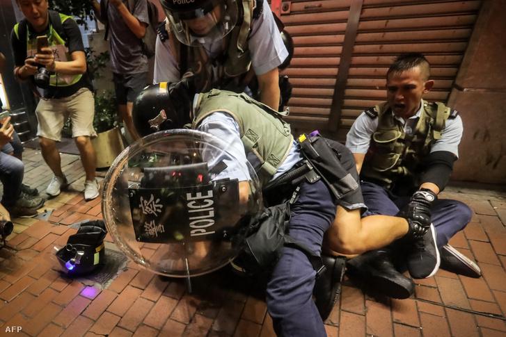Tüntetőt fognak le a rendőrök a hongkongi Mong Kok negyedben 2019. július 7-én