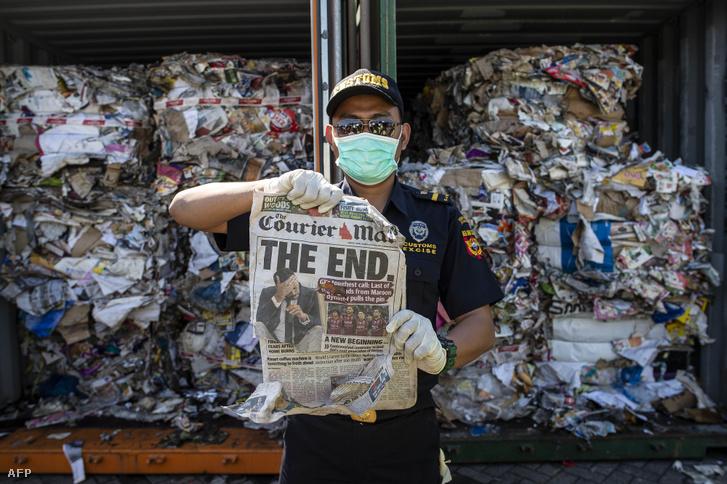 Indonéziai tisztviselő áll az Ausztráliából érkezett veszélyes anyagokat is tartalmazó konténerek előtt a Surabaya kikötőben, amit visszaküldenek a származó országba 2019. július 9-én
