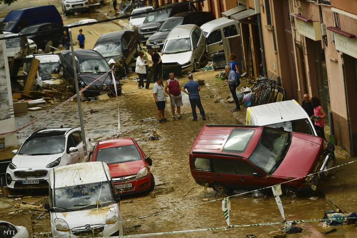 Megrongált autók között emberek az észak-spanyolországi Navarra tartományban fekvő Tafallában 2019. július 9-én miután a nagy mennyiségű eső áradásokat okozott a térségben. Egy férfi életét vesztette akinek autóját elsodorta a víz.