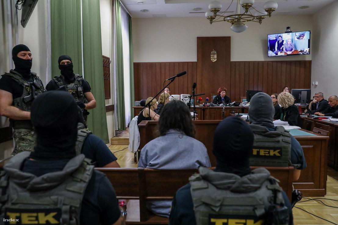 Jozef Rohác (jobb fent a kivetítőn) meghallgatása a Prisztás-gyilkossággal vádolt Portik Tamás (középen háttal) és H. István megújított pere pénteken a Fővárosi Törvényszéken 2019. június 14-én