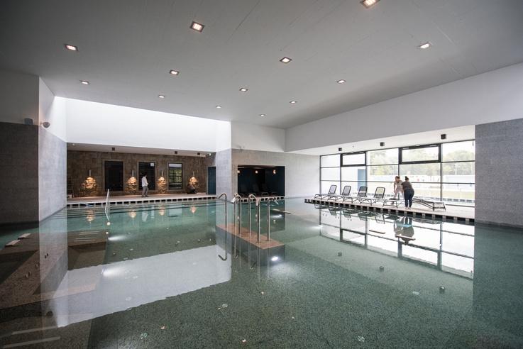 A fürdő központi medencéje a stéghatású járófelületekkel. Háttérben a török fürdő épületének kőfala