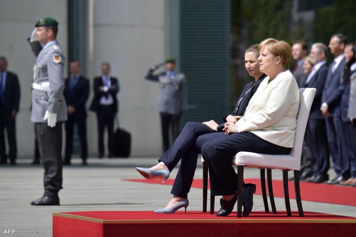 Mette Frederiksen, Dán miniszterelnök és Angela Merkel a nemzeti himnuszok hallgatása közben Berlinben 2019. július 11-én