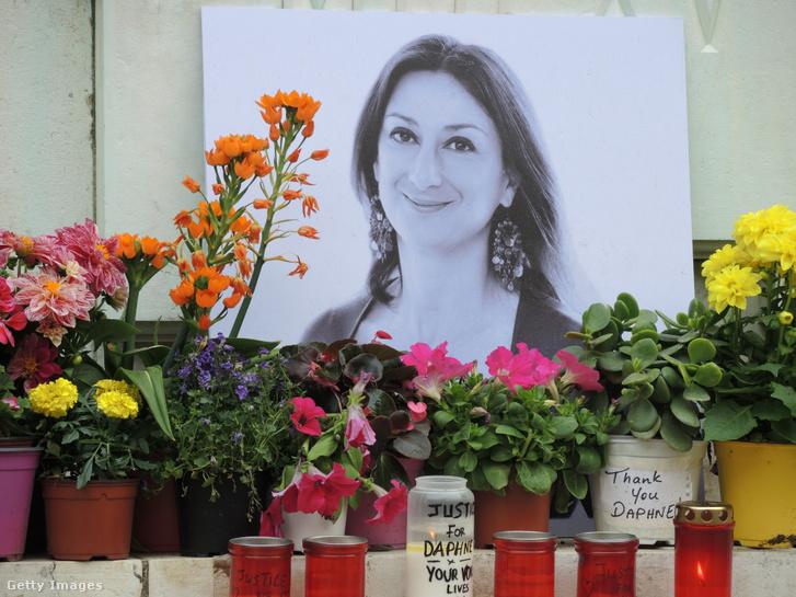 Daphne Caruana Galizia fotója és virágok egy emlékmű lábánál Máltán 2018. április 10-én.