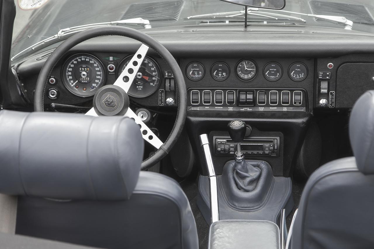 Amennyire lélegzetelállítóan gyönyörű a Jaguar E Type gúnyája, annyira egyszerű és célra törő a belseje. Éles a kontraszt a művészi vonalak és a meglehetősen ingerszegény, fekete belső között. Ettől még persze kéne, mocskosul, a gagyi rádió nélkül