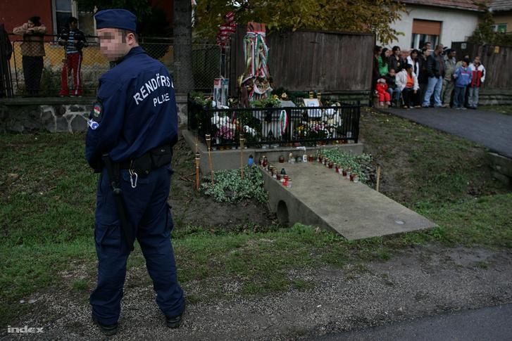 Rendőrök biztosítják a helyszínt, amint elővezetik a vádlottakat az olaszliszkai emberölés ügyében tartott helyszíni tárgyalásra az áldozat emlékhelye mellett 2009. október 27-én