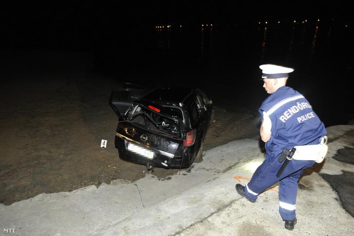 Rendőr helyszínel egy összeroncsolódott személyautónál a nagymarosi kompkikötőnél 2019. július 14-én. A gépjármű a Dunába gurult, a benne tartózkodó férfi életét vesztette.