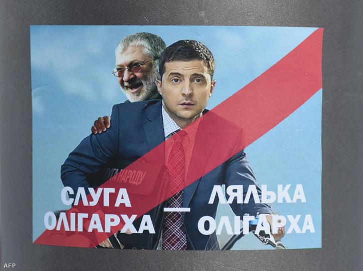 """Egy plakáton az elnökké választott színész, Volodimir Zelenszkij látható a háttérben az oligarcha Igor Kolomojszkijjal 2019. február 8-án Lvivben. """"Oligarcha szolgálója, oligarcha játékszere"""" - hirdeti a felirat."""