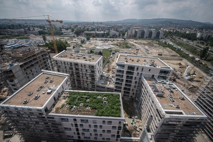 Lakóházcsoport zöldtetőkkel. A házak között nem közterület látszik, hanem a parkoló teteje zöldtetővel
